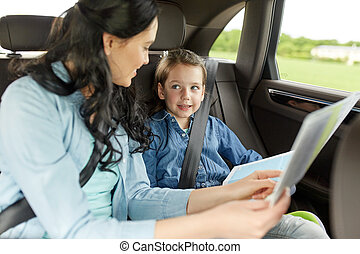 family, transport, road trip and people concept - happy woman and little daughter with map driving in car