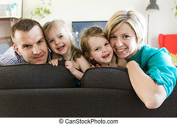 happy family with twin kids on the couch