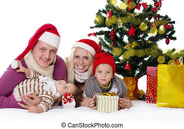 Happy family with two children in Santa hats under Christmas tree over white