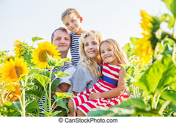 Happy family with two children in sunflowers