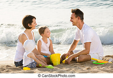 Happy family with two children playing at beach