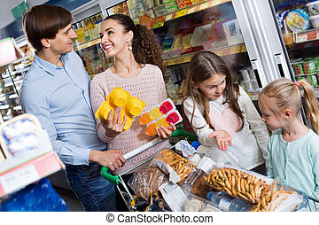 Happy family with two daughters purchasing yoghurts - ...