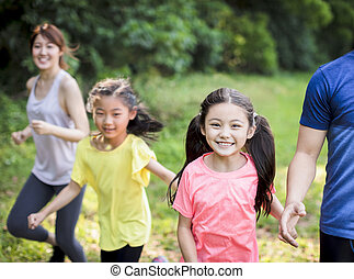 Happy Family with two girls running or jogging in the park
