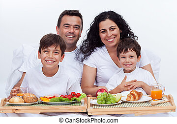 Happy family with two kids having breakfast in bed