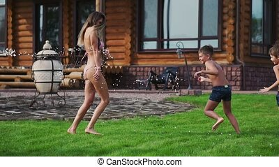 Happy family with two kids playing with garden hose pouring water on grass