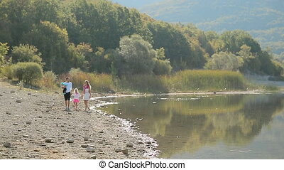 Happy family with two young daughters walking along the lake in slow motion