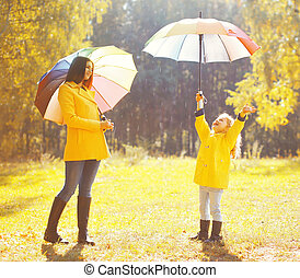 Happy family with umbrellas in sunny autumn rainy day, mother and child enjoying rain
