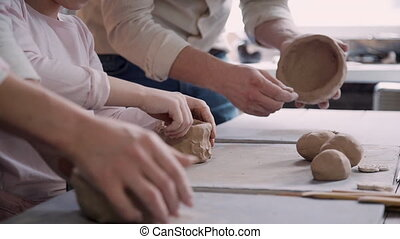 Happy family working with raw and wet clay in workshop room...