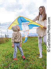 Happy family, young mother woman, little boy son 3-6 years old, emotions delight joy positive. Beige casual wear. They launch kite, laugh relax weekend. Warm casual wear, beige sweater with hood.
