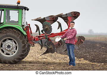 Happy farmer beside plough