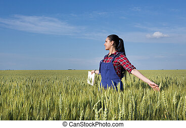 Happy farmer girl in wheat field