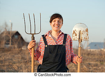 Happy farmer - Happy female farmer with spade and hayfork in...