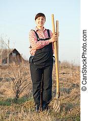 Happy farmer - Happy female farmer with spade and pitchfork...