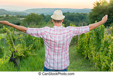 Happy farmer relaxing among the grape rows
