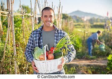 Happy farmer with basket of vegetables in garden
