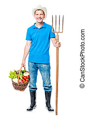Happy farmer with forks and a crop of vegetables on a white background