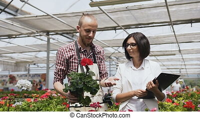 Happy Farmers and Gardeners Work and Examine Flowerpots in...