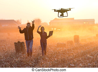 Happy farmers waving hands to drone - Farmer woman with...