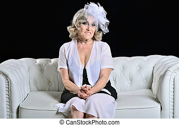 Happy fashionable elderly woman sitting on a white sofa