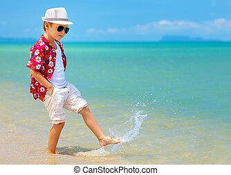 happy fashionable kid boy walking in surf on tropical beach