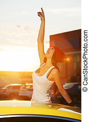 Happy fashionable woman standing at the car