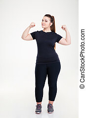 Happy fat woman showing her biceps - Full length portrait of...