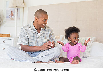 Happy father and baby girl sitting on bed together