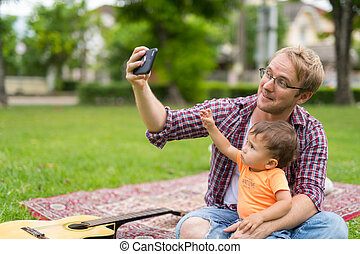 Happy father and baby son taking selfie together outdoors