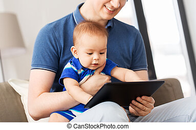 happy father and baby son with tablet pc at home