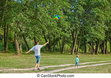 Happy father and child playing in nature in summer