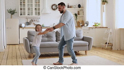 Happy father and cute kid daughter dancing playing in kitchen