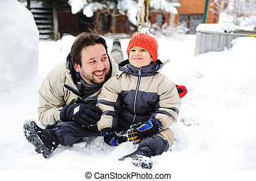Happy father and cute son together on snow in front of house