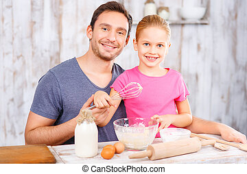 Happy father and daughter baking together