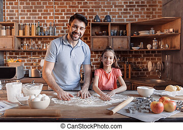 'Happy father and daughter cooking together and smiling at camera