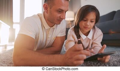 Happy father and daughter enjoying time together and using a tablet for family entertainment while lying on a floor in living room at home. Concept of a happy family and quality leisure time