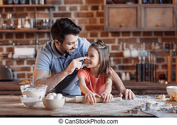 'Happy father and daughter having fun while cooking together