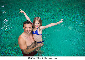 Happy father and daughter in pool