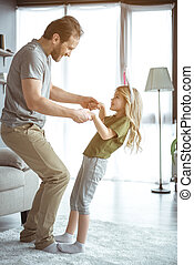 Happy father and daughter moving with joy in living room