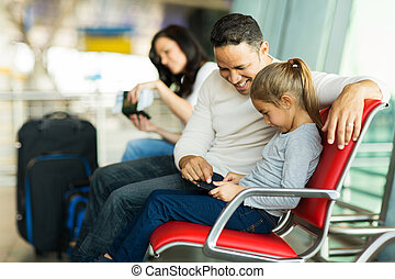 father and daughter using tablet computer at airport