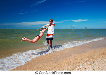Happy father and his daughter at the beach having fun