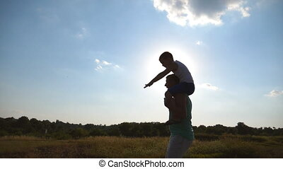 Happy father and his little son on the shoulders running in green field on sunset. Child sits on dad on meadow in sunny day and playing airplane. Daddy and boy having fun together. Slow motion