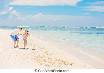 Happy father and his small son having great quality family time enjoying white sand ocean beach on summer holidays