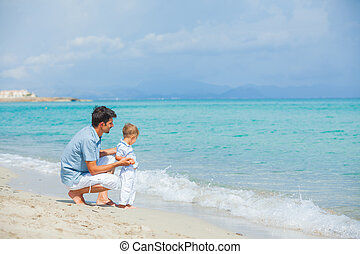 Happy father and his son playing at beach