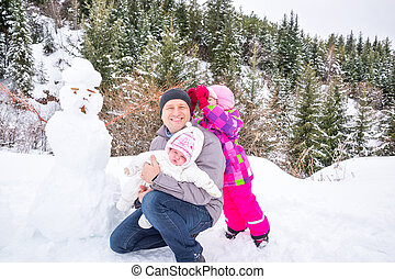 Happy father and his two daughters building a snowman on winter day. Family playing on nature with forest in background. Christmas time