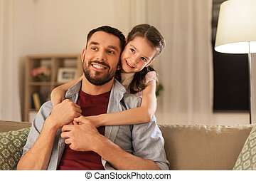 happy father and little daughter hugging at home