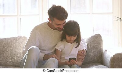 Happy father and little daughter using smartphone sit on...