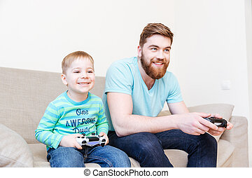 Happy father and little son playing video games