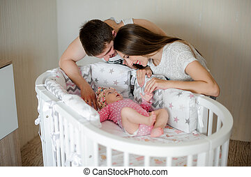 Happy father and mother lulling cute little newborn baby girl in bed