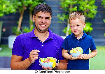 happy father and son enjoying fresh fruit salad