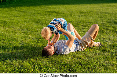 Happy father and son having fun outdoor on meadow